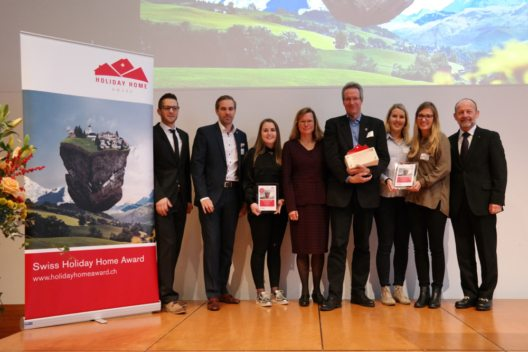 Personen auf dem Bild von links nach rechts: Daniel Koller (e-domizil AG), Martin Nydegger (Schweiz Tourismus), Andrea Parpan (Lenzerheide), Barbara Gisi (STV), Stefan Sieber (Engadin St. Moritz), Jasmin Della Torre und Michèle Feierabend (Engelberg-Titlis), Dominique de Buman (Nationalrat und Präsident STV) (Bild: © Swiss Holiday Home Award / e-domizil AG)